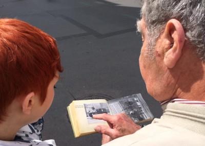 Unser Zeitzeuge Heinz Schäfer mit Fotoalbum am Checkpoint Charlie. Wir spitzen die Ohren.